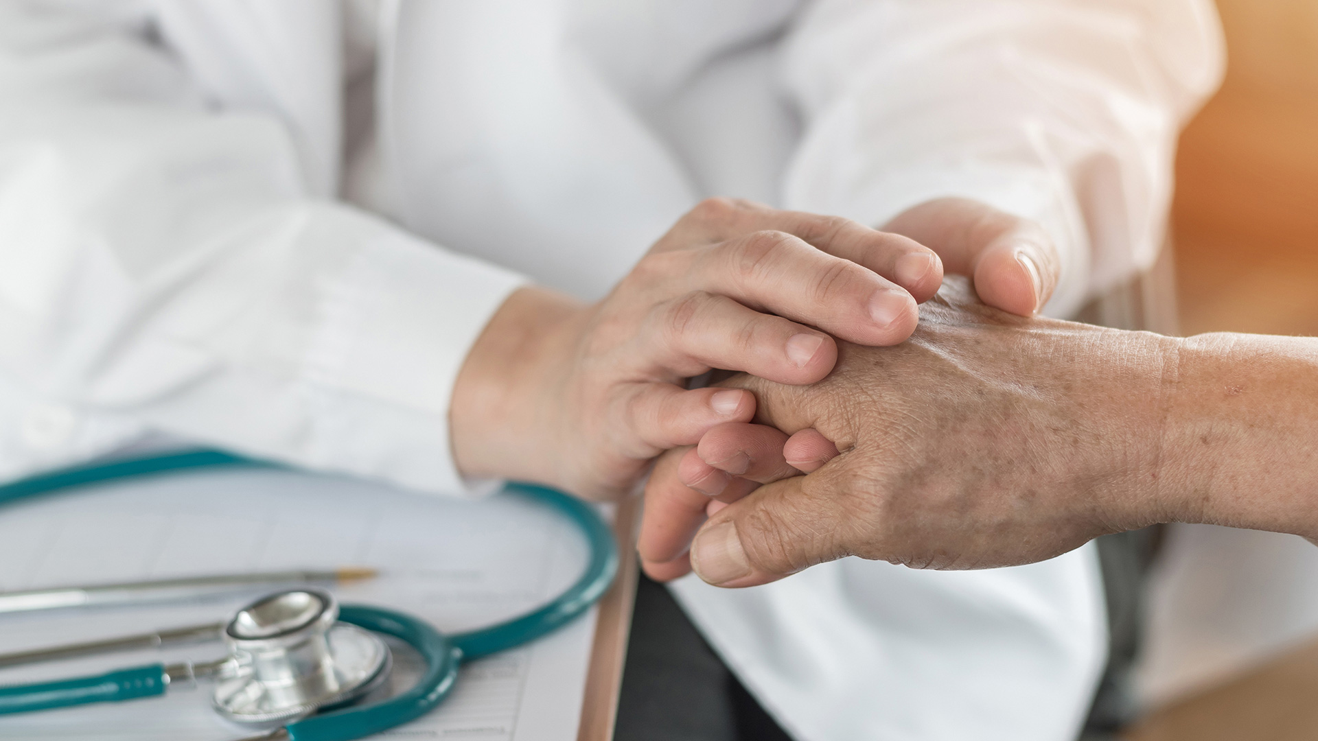 Doctor in a white coat holding a patient's hand.
